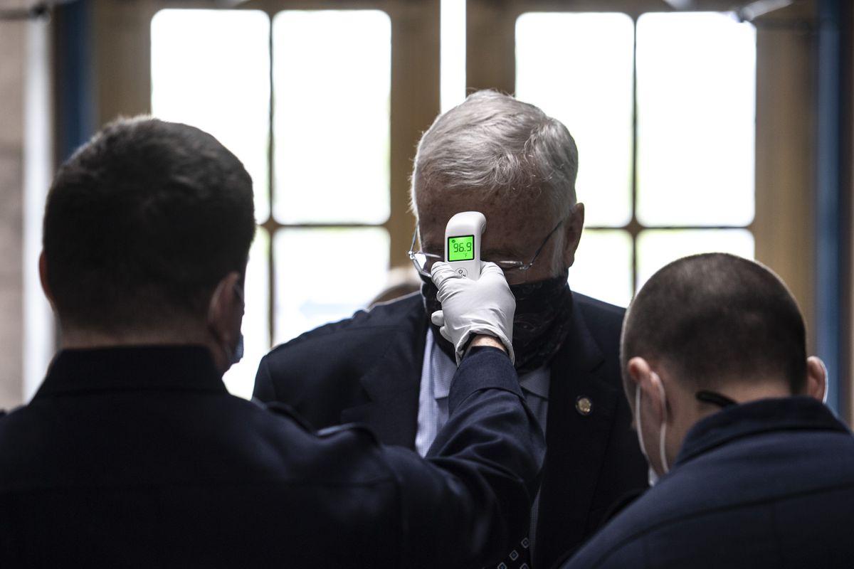 Sen. Gary Stevens, R-Kodiak, has his temperature taken by Capital City Fire/Rescue personnel as Alaska legislators return to the Capitol in Juneau on Monday, May 18, 2020. (Photo by Michael Penn)