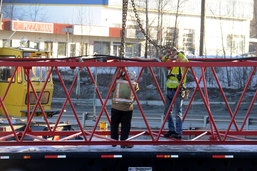 Workers prepare a section of crane derrick to be unloaded from a flat bed trailer at the Artillery Road overpass on the Glenn Highway on Friday, March 23, 2018. A truck transporting a modular building crashed into the bridge on Wednesday causing extensive damage. (Bob Hallinen / ADN)