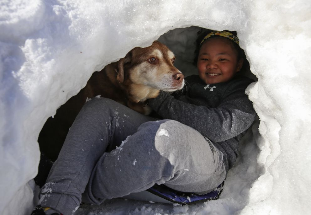 Nadia Green sits with her dog, Jewels, inside the quinzee she built. (Emily Mesner / ADN)