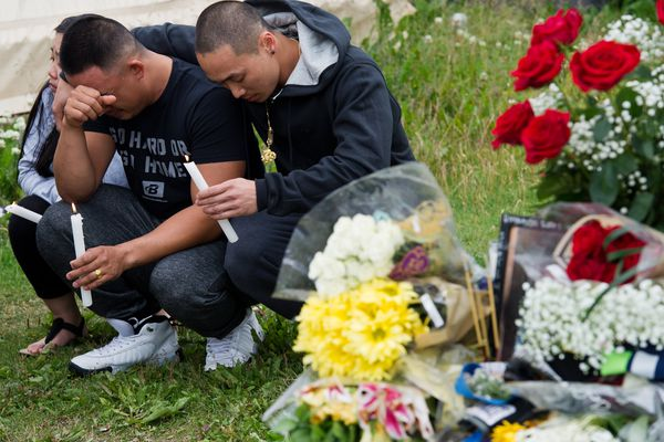 """Souchoy Saephanh, left, father of Reynaldo Khotesouvan, is comforted at the vigil.About 100 people stood in a semi-circle on Bliss Street in Anchorage's Mountain View neighborhood Monday to remember a 15-year-old boy who was killed at that spot last week. Police said Raynaldo Khotesouvan was shot. A photo of Khotesouvan was partially obscured by a table that overflowed with flowers, candles and written remembrances Monday. A few people spoke up to remember Khotesouvan as kind, fun and athletic. Most of the emotional ceremony was silent. Two Anchorage Police officers stood nearby. Sixteen-year-old Luimariamofoa Polu was arrested and charged with first-degree murder in the incident. At the conclusion of the event, Siou Khotesouvan, Reynaldo's mother, said the turnout meant a lot to her. """"It gives me some peace and comfort that the community's coming together and supporting one another,"""" she said. """"Gun violence needs to stop,"""" she added. """"No more blood."""" (Marc Lester / ADN)"""
