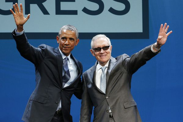 President Barack Obama, left, and Senate Minority Leader Sen. Harry Reid wave onstage at the National Clean Energy Summit on Monday in Las Vegas. The president used the speech to announce a set of executive actions and other efforts aimed at making it easier for homeowners and businesses to invest in green energy improvements.