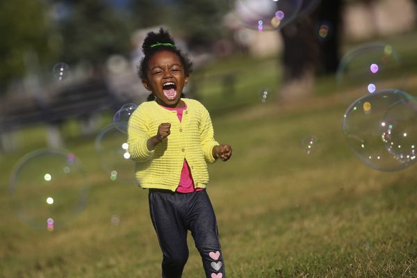 Seraphina Jones-Perez, 3, cheers with joy as she plays with bubbles her father, Lirio Perez, made for her while they enjoy a sunny evening at Delaney Park in Anchorage on Aug. 4, 2020. (Emily Mesner / ADN)