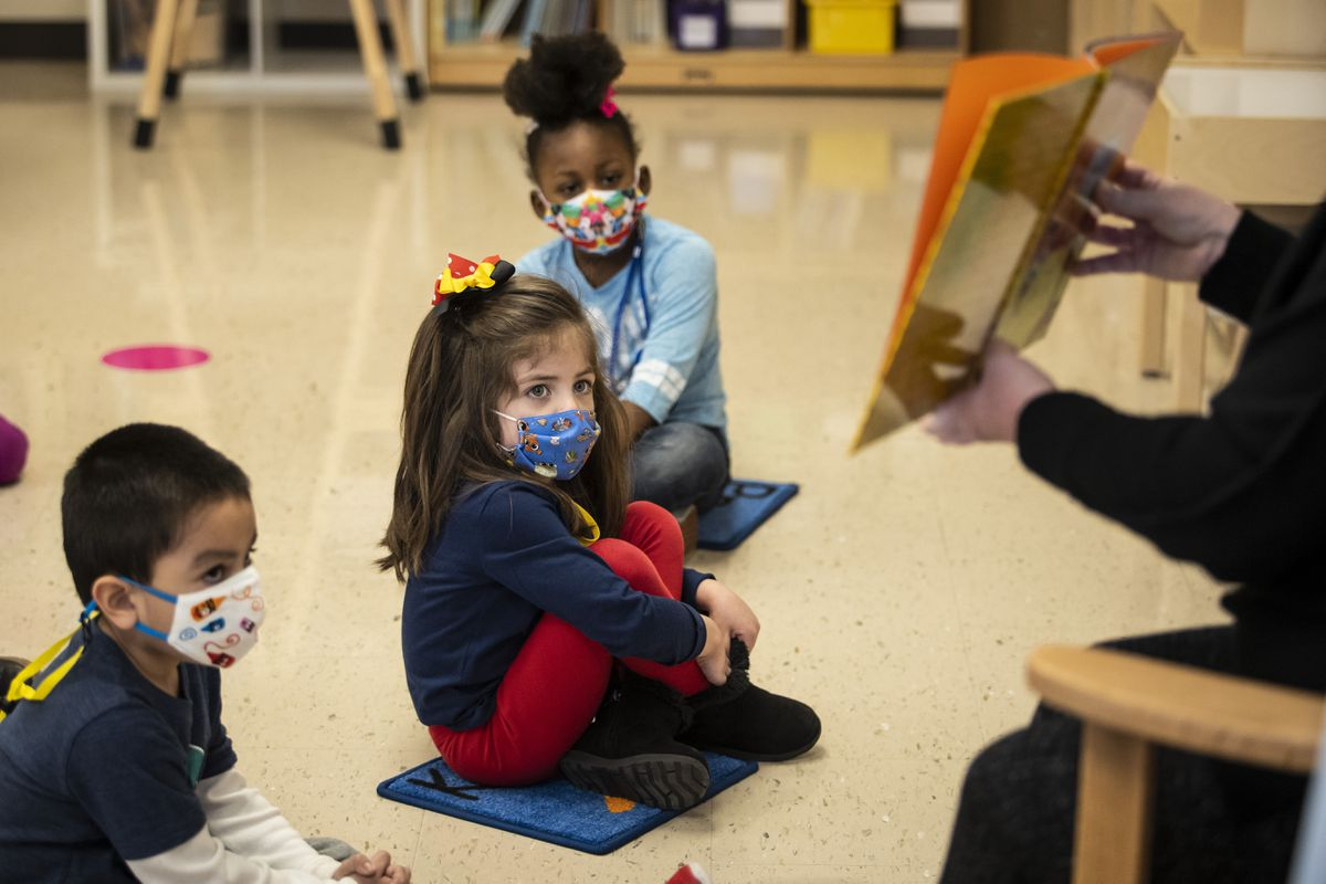 Pre-kindergarten students listen as their teacher reads a story at Dawes Elementary in Chicago, Monday, Jan. 11, 2021. Chicago Public Schools students began their return to the classroom Monday as school doors opened to thousands of pre-kindergarten and some special education students after going remote last March due to the coronavirus pandemic. (Ashlee Rezin Garcia/Chicago Sun-Times via AP, Pool)