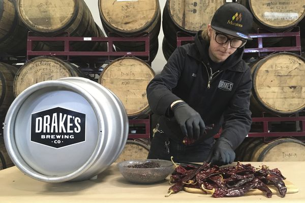 In this photo taken May 10, 2019, Hal McConnellogue, cellar manager at Drake's Brewing Company, works on putting chipotle peppers into a cask used to infuse beer with unique flavors in San Leandro, Calif. As craft breweries have boomed, competition for attention has intensified and that has a lot of brewers looking for ways to differentiate themselves by introducing strange new flavors. (AP Photo/Haven Daley)