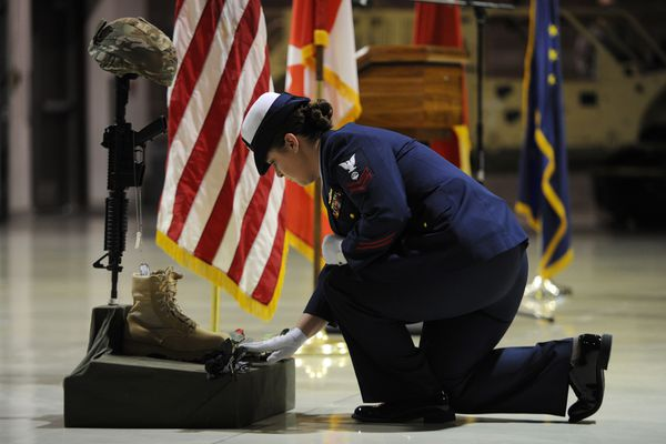 U.S. Coast Guard Petty Officer Linzi Hargraves placed red roses during a Fallen Warrior ceremony during Veterans Day ceremony at the Alaska National Guard armory on Joint Base Elmendorf-Richardson on Sunday, Nov. 11, 2018, on the 100th anniversary of the end of WWI. The ceremony honored the men and women who have served in the armed forces. (Bill Roth / ADN)