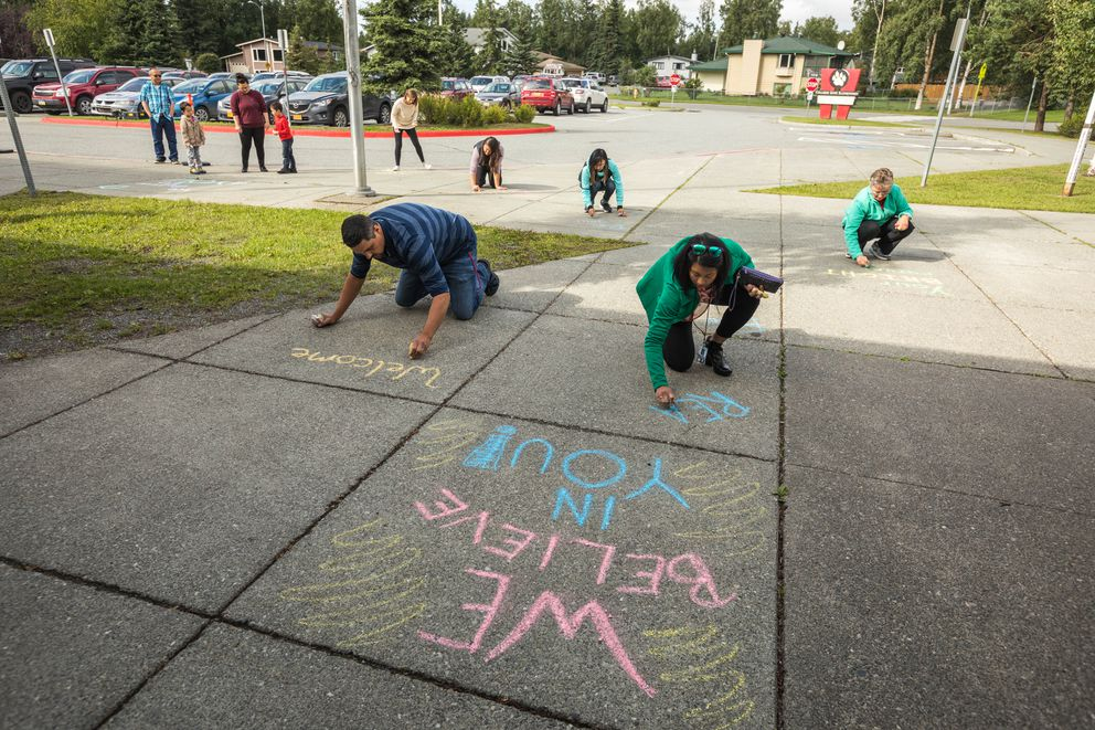 Fifth-grade teachers Jack Hopkins, left, and Stephanie Wooten write inspirational messages in chalk outside the front of College Gate Elementary on Friday. (Loren Holmes / ADN)