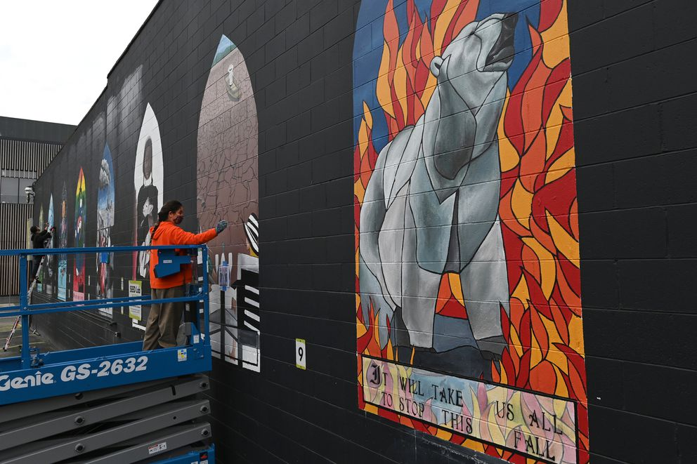 Artist Lina Villar works on her painting 'Blissfully Unaware, ' part of the climate change mural going up on the SEED Lab in downtown Anchorage on Tuesday, Sept. 22, 2020. (Bill Roth / ADN)