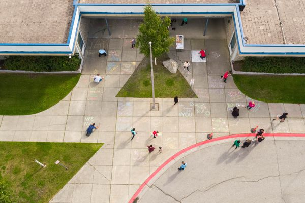 Teachers and community members write inspirational messages in chalk outside the front of College Gate elementary school on Friday, Aug. 17, 2018. United Way organizes the annual Chalk the Walks event, writing inspirational messages outside Anchorage area schools. (Loren Holmes / ADN)