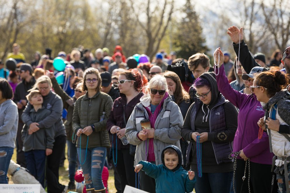 Participants in the Out of Darkness Community Walk hold up beads Saturday on the Delaney Park Strip to remember loved ones lost to suicide. (Loren Holmes / ADN)
