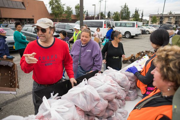 Tom Shanks, left, and his wife, Patty Shanks, receive food from the Mobile Food Pantry on Saturday. Over 100 households received perishable food at the biweekly event. (Loren Holmes / Alaska Dispatch News)