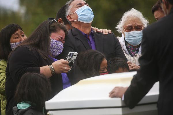 Clarissa Coffin, left, leans on Scott Wells' shoulder, center, as they stand next to Amanda Bouffioux's casket alongside family and friends and grieve before her burial at the Anchorage Memorial Park Cemetery on Sept. 15, 2020. Bouffioux tested positive for COVID-19 in August and spent three weeks on a ventilator before she died Sept. 8. Coffin, who was FaceTiming their mother, Edna, is Amanda's sister and Wells is her partner. (Emily Mesner / ADN)