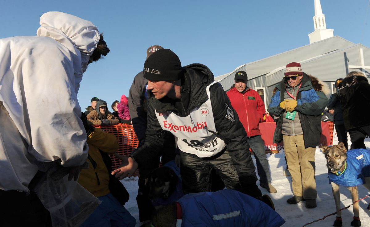 Iditarod musher Dallas Seavey, right, reaches out to shake hands with Nicolas Petit after they finished second and third, respectively, in the 2017 Iditarod Trail Sled Dog Race on Tuesday. (Bob Hallinen / Alaska Dispatch News)