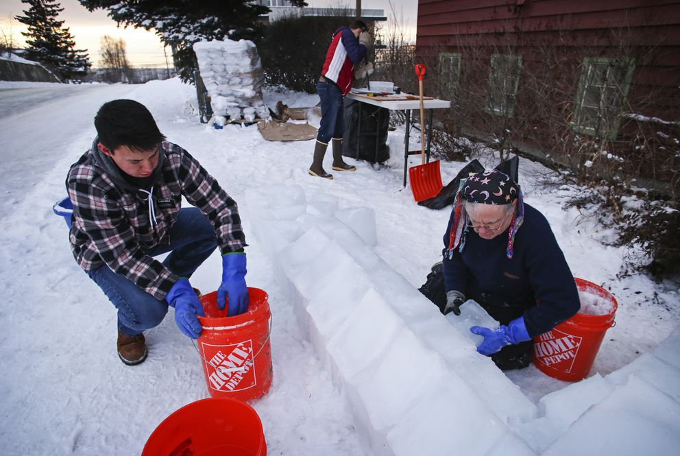 Hayden Riddle, left, and Nathanael Busath, center, help Tommy O'Malley construct the base of the ice sculpture. (Emily Mesner / ADN)