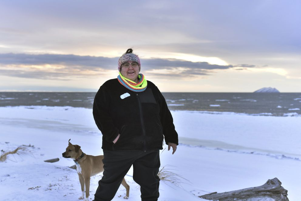 In this Jan. 14, 2019 photo, Clarice 'Bun ' Hardy stands on the beach with her dog, Marley, in the Native Village of Shaktoolik, Alaska. Hardy, a former 911 dispatcher for the Nome Police Department, says she moved back to her village after a sexual assault left her feeling unsafe in Nome. (AP Photo/Victoria Mckenzie)
