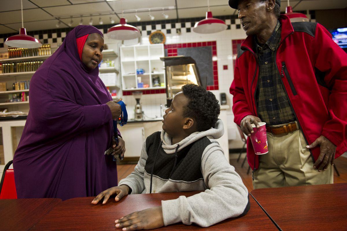 Asha Artan, who co-owns Safari Restaurant, talks with her son, Said Eprahin, and Mohamed Shide. (Marc Lester / Alaska Dispatch News)