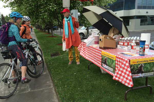 The Alaska Dispatch News stand for Bike to Work Day, at 31st Avenue and C Street, offers bagels and cream cheese, coffee and papers to two-wheeled commuters Wednesday morning. (Anne Raup / Alaska Dispatch News)