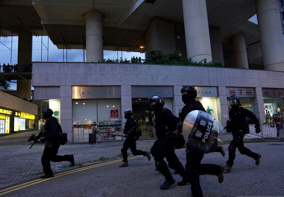 Policemen arrive to arrest protesters after they set fire to barricades and vandalized signages at Tung Chung near airport in Hong Kong, Sunday, Sept.1, 2019. Train service to Hong Kong's airport was suspended Sunday as pro-democracy demonstrators gathered there, while protesters outside the British Consulate called on London to grant citizenship to people born in the former colony before its return to China. (AP Photo/Vincent Yu)