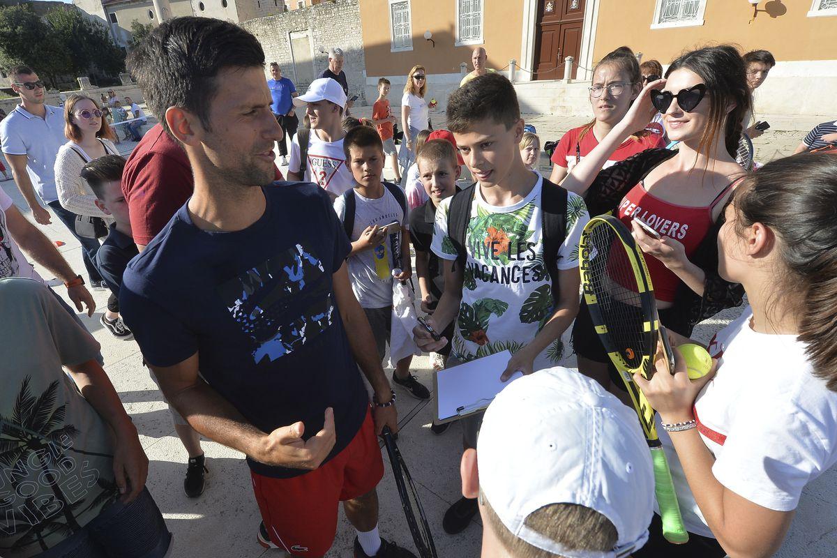 In this photo taken June 18, 2020, Serbian tennis player Novak Djokovic, left, talks to children in Zadar, Croatia. Novak Djokovic has tested positive for the coronavirus after taking part in a tennis exhibition series he organized in Serbia and Croatia. (AP Photo/Zvonko Kucelin)