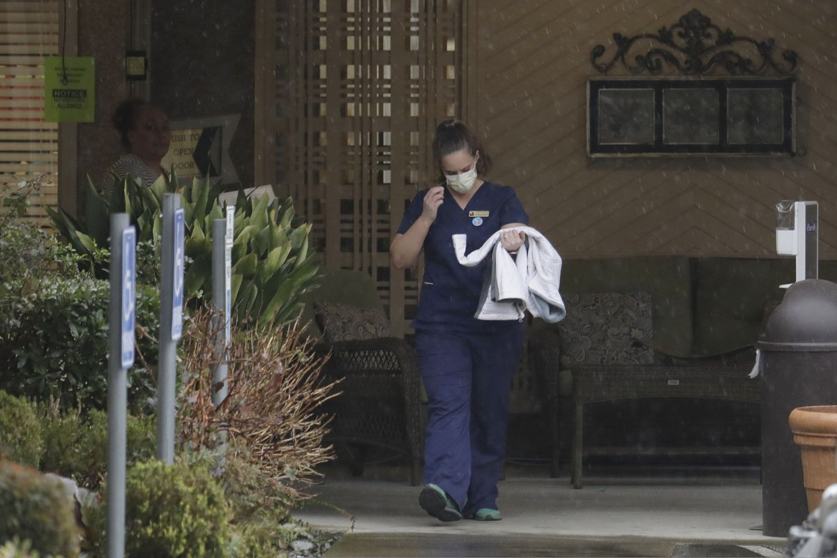 A worker at the Life Care Center in Kirkland, Wash., near Seattle, wears a mask as she leaves the building, Monday, March 2, 2020. Several of the people who have died in Washington state from the COVID-19 coronavirus were tied to the long-term care facility, where dozens of residents were sick. (AP Photo/Ted S. Warren)