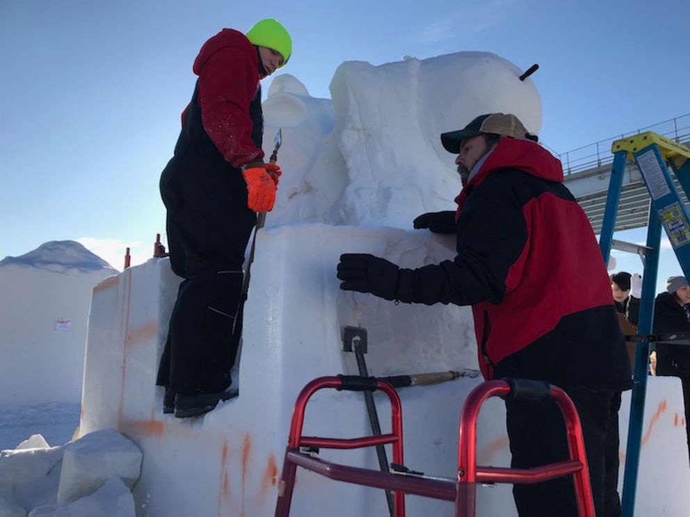 Wade Pier talks with 12-year-old Dustty Heckel about where to carve on the block of snow on Sunday, February 23, 2020, to prepare for the annual Fur Rendezvous' Alaska State Snow Sculpture Championship. (Tess Williams / ADN)