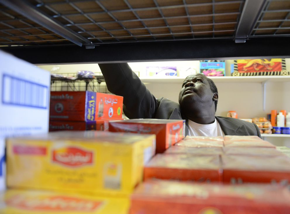 William Riek straightens up the shelves at Banadir Halal Market at Boniface Parkway and Northern Lights Boulevard in Anchorage on Friday. (Bob Hallinen / Alaska Dispatch News)
