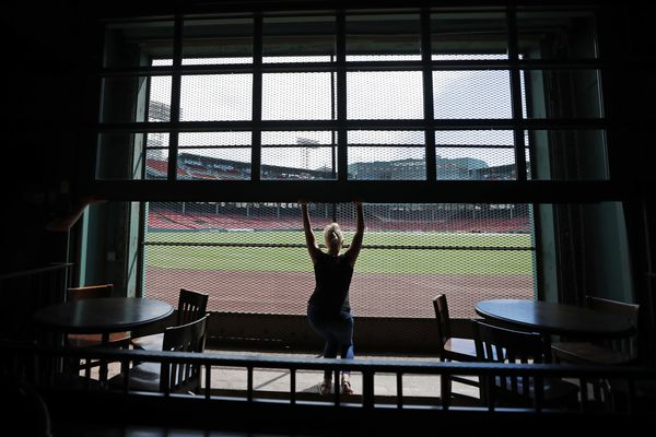 In this June 25, 2020, photo, general manager Maggie Flynn opens a large window with a view of Fenway Park from the Bleacher Bar in Boston. Located inside the outfield structure at Fenway, it might be one of the few places where fans can watch live MLB baseball this year. Like the Knothole Gangs of the sport's early days, fans hoping to catch a glimpse of a ballgame in person this season will be pressing their faces up against hotel windows, peering through metal grates or clambering up to rooftops when baseball returns this month in otherwise empty stadiums. (AP Photo/Elise Amendola)
