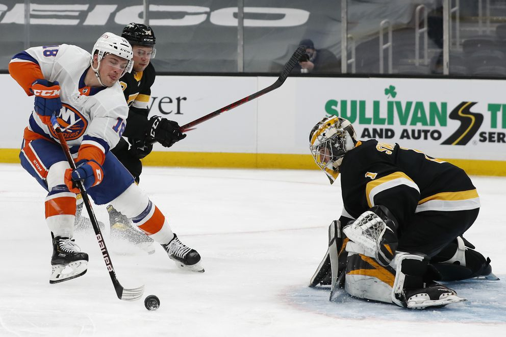 New York Islanders' Anthony Beauvillier reaches for the puck in front of Bruins goaltender Jeremy Swayman on Friday. (Winslow Townson / Associated Press)
