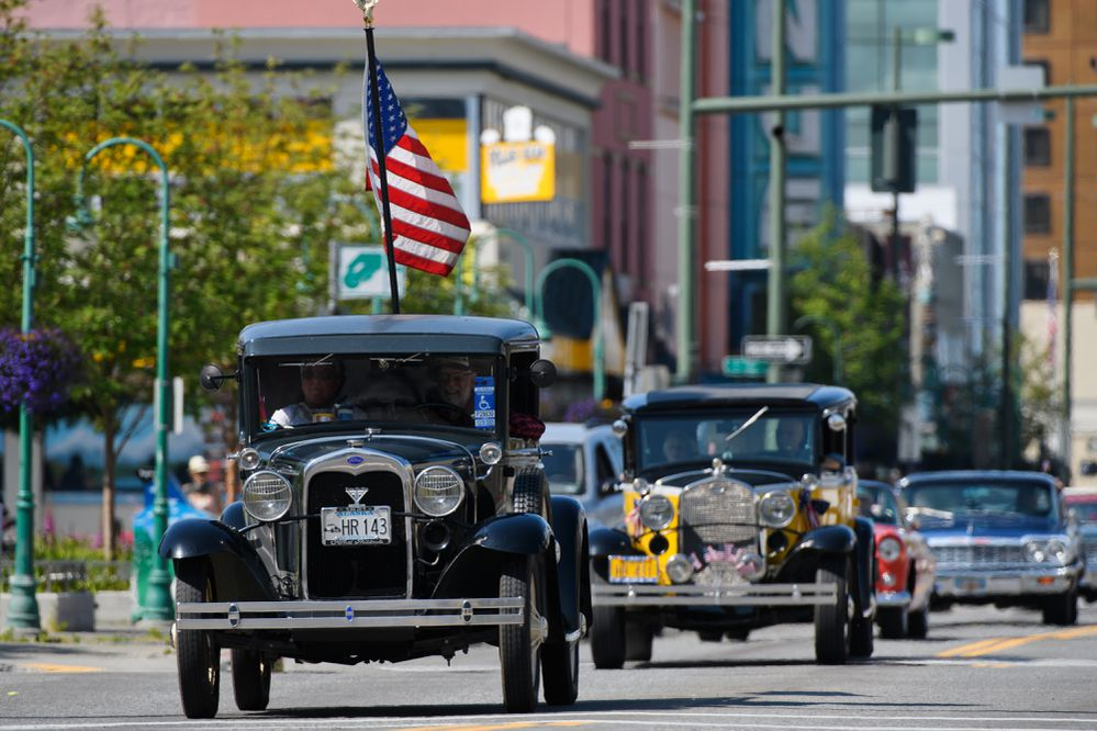 Carl Godsoe drives a 1931 Ford Model A pickup and carries the US flag as drivers from the Antique Auto Mushers of Alaska head east on Fourth Avenue on July 4, 2020. (Marc Lester / ADN)