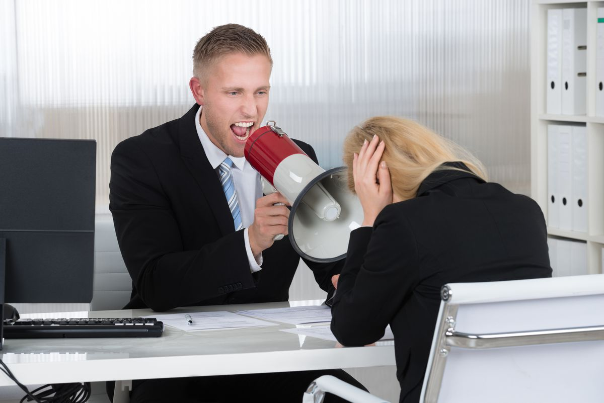 Boss shouting at businesswoman through loudspeaker at desk in office. (Thinkstock)