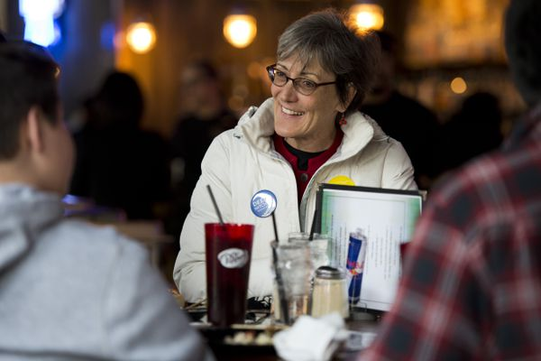 Anchorage School Board candidate Deena Mitchell talks with others at Flattop Pizza on April 3, 2018. (Marc Lester / Anchorage Daily News)