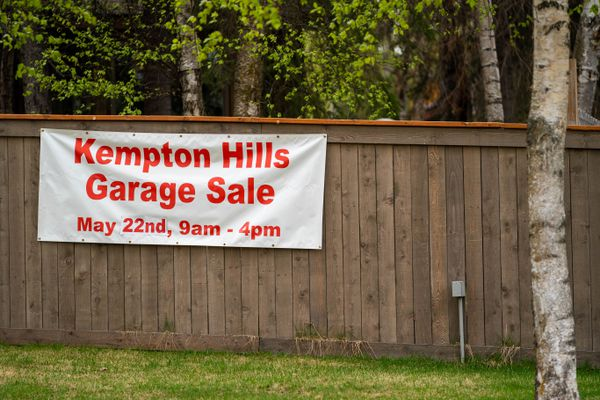 A sign for the annual Kempton Hills garage sale is seen on a fence on Wednesday, May 19, 2021. The popular neighborhood event will take place this year on Saturday, May 22. (Loren Holmes / ADN)