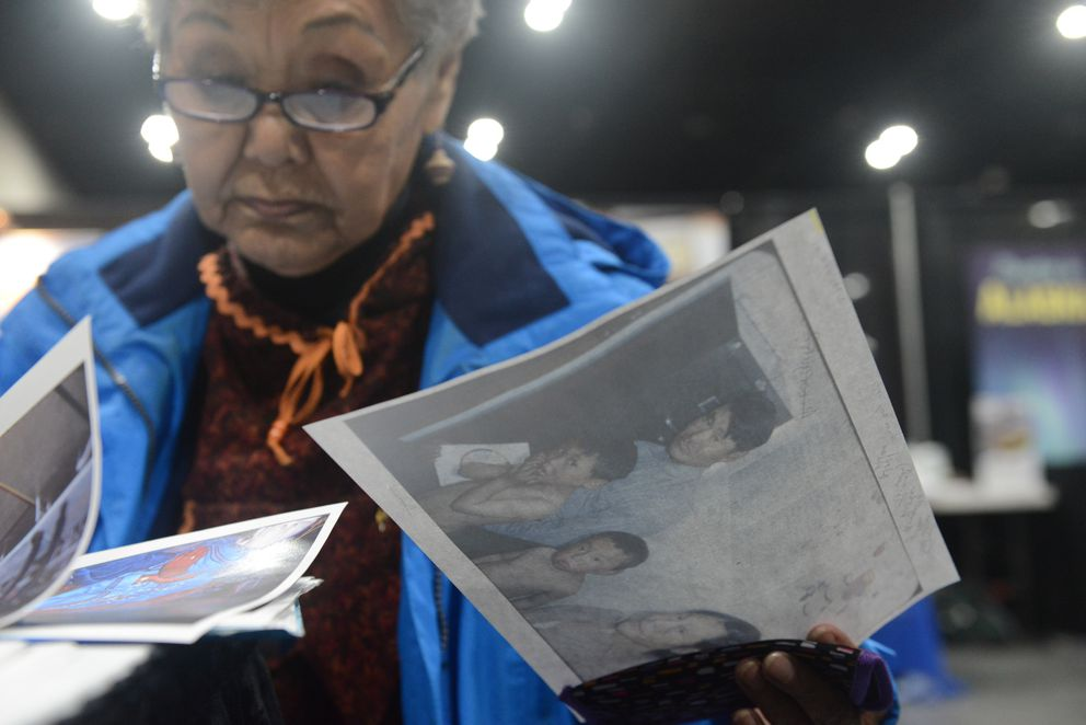 Gemma Gaudio holds a photograph of her father, mother and brothers from Hooper Bay, AK at the Anchorage Museum booth at AFN. (Bob Hallinen / ADN)
