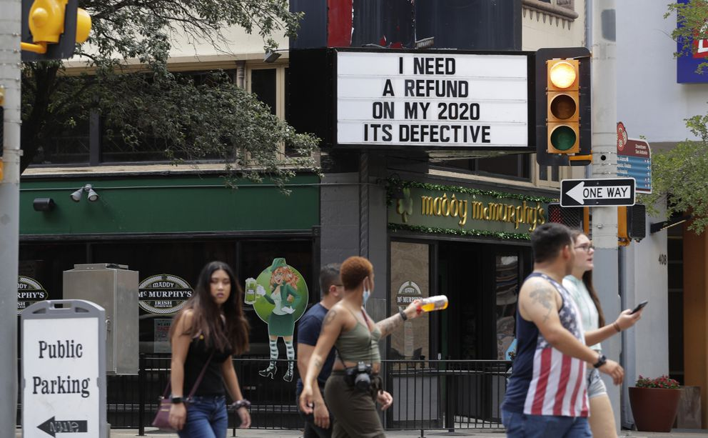Visitors, some wearing masks to protect against COVID-19, walk through downtown San Antonio, Monday, July 20, 2020. Cases of COVID-19 continue to spike in Texas. (AP Photo/Eric Gay)