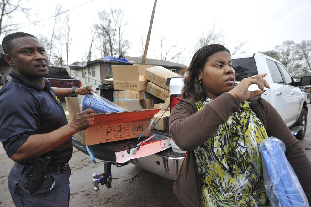 Shanika Mack, right, of Edwards, gets tarpaulin from Tracy Funches, left, with the Hinds County Emergency Operation Center, to cover damaged areas of her mother's home after a tornado ripped through their neighborhood around noon, Monday, Dec. 16, 2019, in Edwards, Miss. Mack's mother was home alone at the time of the storm but unharmed. (Barbara Gauntt/The Clarion-Ledger via AP)