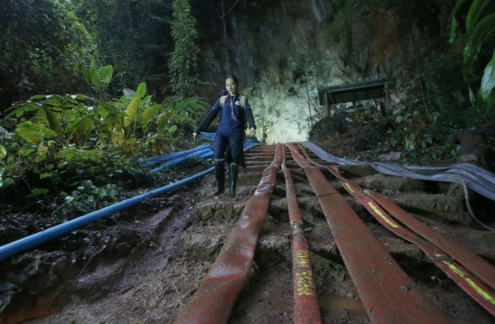 FILE - In this Friday, June 29, 2018, file photo, a rescuer makes her way down muddy steps past water pump hoses at the entrance to a cave complex where it's believed that 12 soccer team members and their coach went missing, in Mae Sai, Chiang Rai province, in northern Thailand. For the boys and their coach, we have only a hint of what it might have been like. But for the rest of us, watching from afar as the world's journalists beamed us live shots and the unknowable became known drip by captivating drip, we knew only one thing: It was hard to look away. (AP Photo/Sakchai Lalit, File)