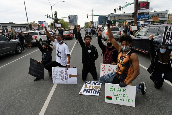 """Protestors momentarily kneel in traffic on Northern Lights Boulevard. A crowd gathered in the parking lot of the Midtown Mall and along the sides of Northern Lights Boulevard Saturday, May 30, 2020, for the """"I Can't Breathe"""" protest against police brutality. (Marc Lester / Anchorage Daily News)"""