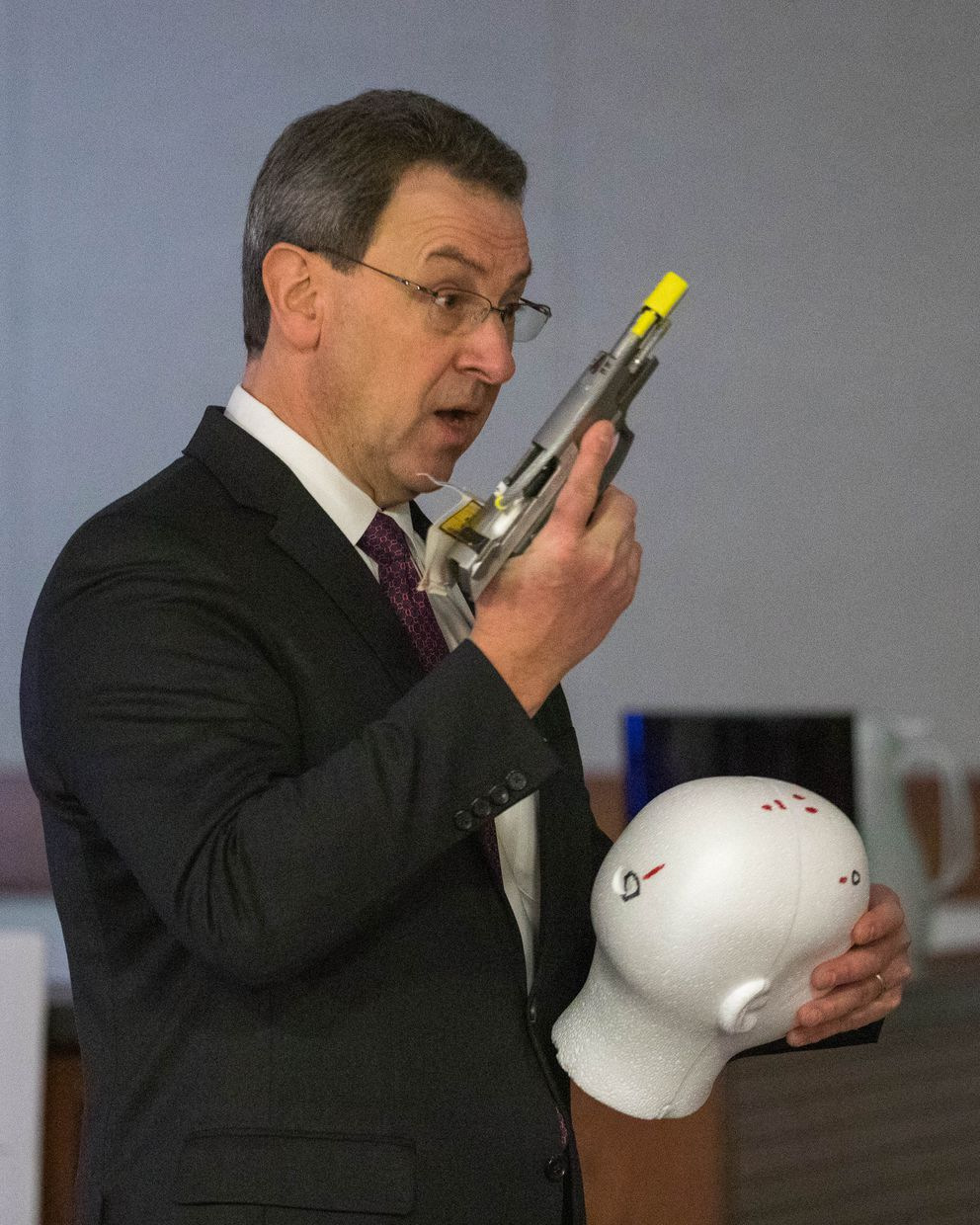Palmer District Attorney Roman Kalytiak on Wednesday holds a gun that was used to pistol-whip David Grunwald. Kalytiak is also holding a model of the victim's head, showing injuries from the beating and a gunshot. (Loren Holmes / ADN)