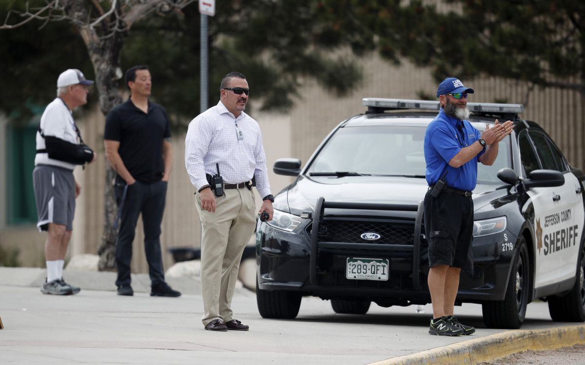 School police officers look on as students leave Columbine High School late Tuesday, April 16, 2019, in Littleton, Colo. Following a lockdown at Columbine High School and other Denver area schools, authorities were looking for a woman suspected of making threats who was later found dead in an apparent suicide. (AP Photo/David Zalubowski)