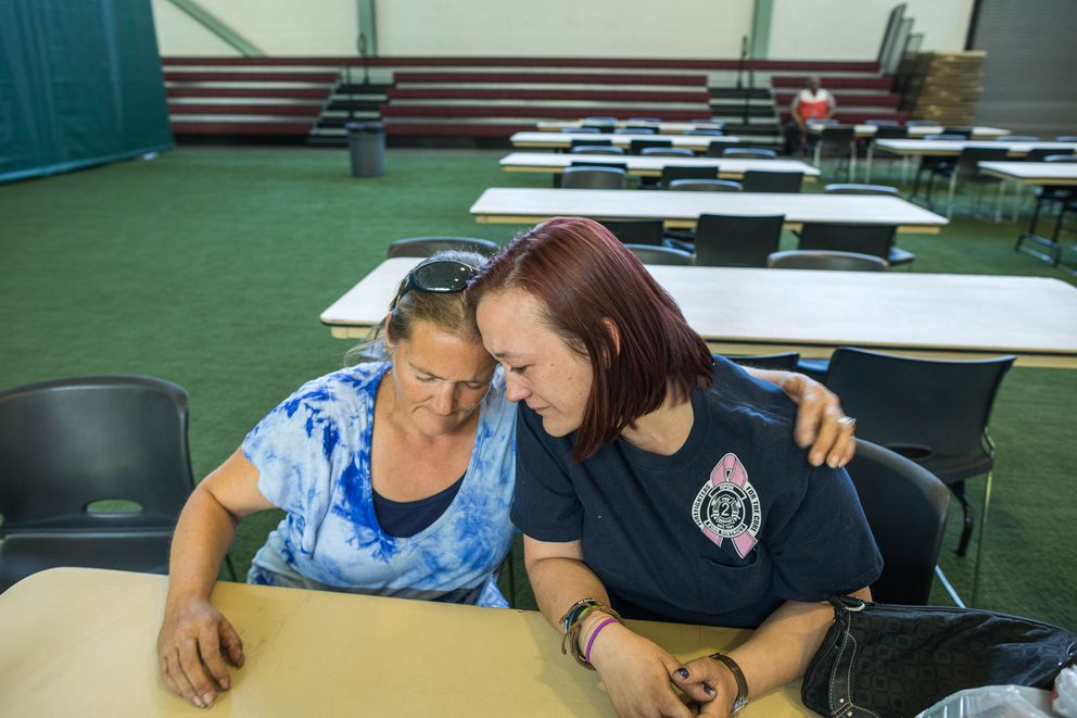 Miranda Bennett hugs her neighbor Ashley Johnson on Wednesday, Aug. 21, 2019 at a Red Cross shelter at the Menard Sports Center in Wasilla. Johnson lost her home in the McKinley Fire. (Loren Holmes / ADN)