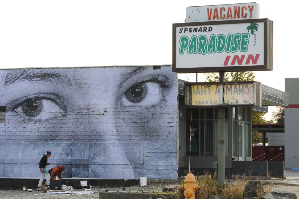 Artist James Temte and photographer Michael Conti collaborated on a wheat paste mural installation on a building next to the vacant lot where the Paradise Inn once stood in Spenard on Sunday, Sept. 22, 2019. (Bill Roth / ADN)