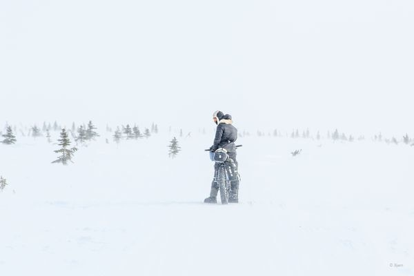 Kim McNett pauses in a blizzard outside of the village of Koyuk in March 2016. Bjørn Olson and Kim McNett biked from Nome to Kivalina in the late-winter/early spring of 2016 and encountered many storms and tough conditions during their trip. (Bjørn Olson)