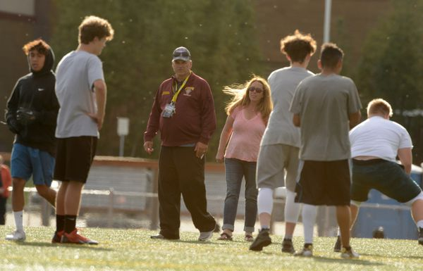 Brad Lauwers, third from left, and Kathleen Navarre run a no-pads football practice Friday that marked the end of the Dimond football program's suspension. (Bob Hallinen / ADN)