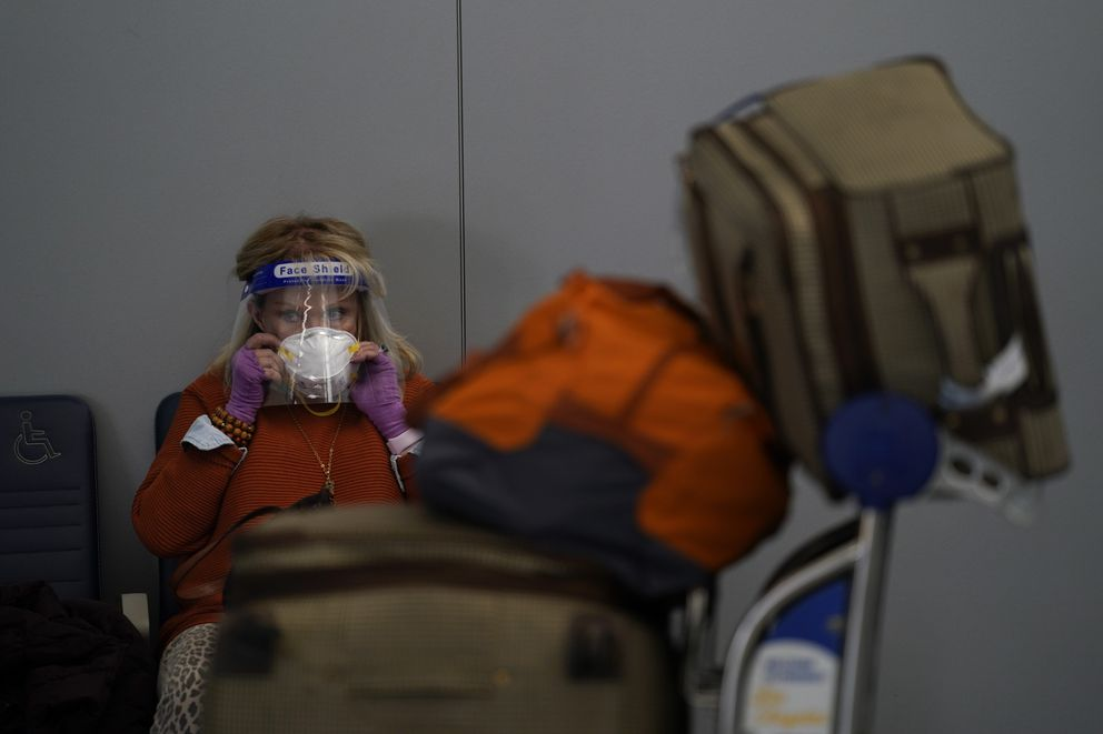 A traveler adjusts her mask while waiting to check in for her flight at the Los Angeles International Airport in Los Angeles, Monday, Nov. 23, 2020. (AP Photo/Jae C. Hong)