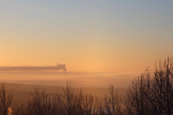 A layer of ice fog blankets the Fairbanks valley Wednesday afternoon, Jan. 18, 2017. The plume from the downtown powerplant drifts off to the southeast after rising above the fog. (Dermot Cole / Alaska Dispatch News)