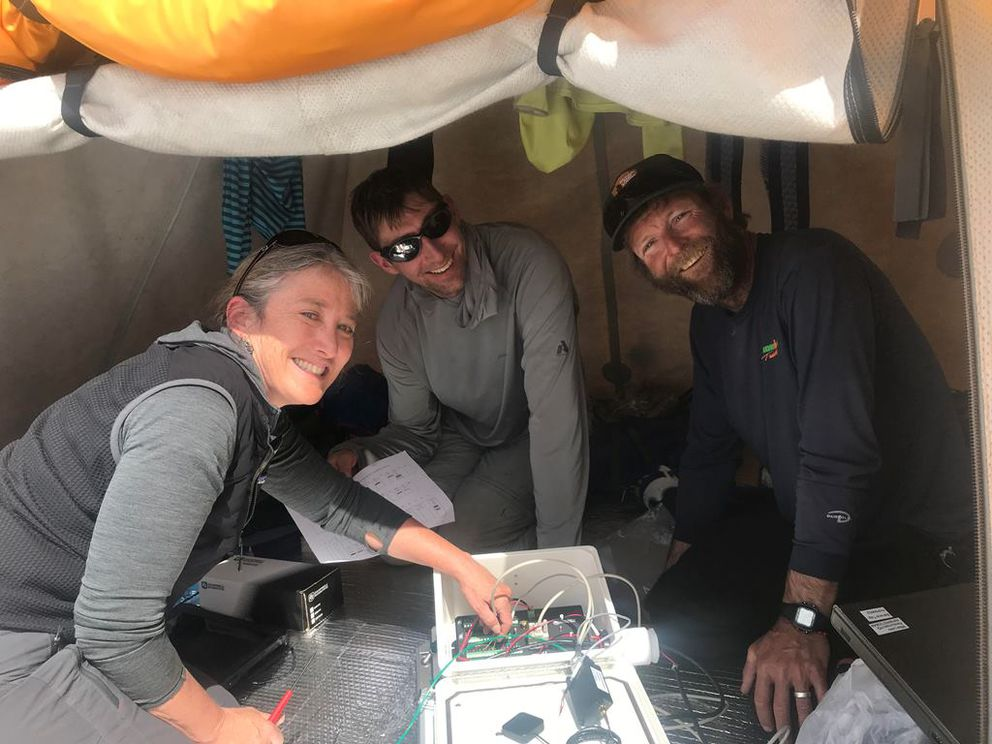 Scientists Pam Sousanes, Dom Winski, and Michael Loso programming the base camp weather station. (Photo by Tucker Chenoweth / NPS)