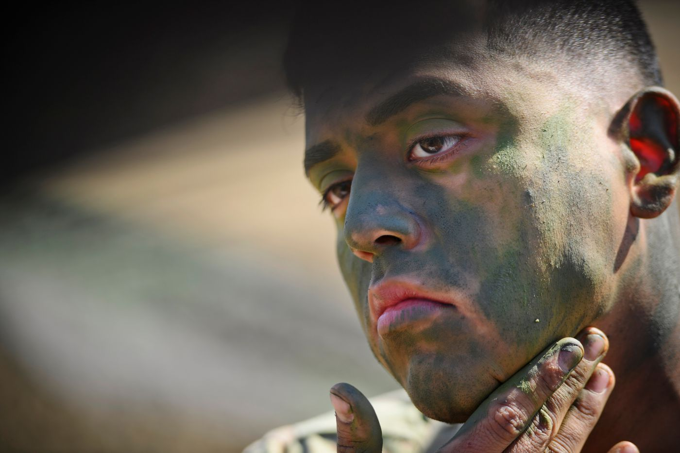 Pfc. Angel Castillo applies camouflage face paint during testing. (Marc Lester / ADN)