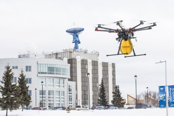 A Ptarmigan drone carrying a test payload, flies in front of the UAF Geophysical Institute in Fairbanks, AK on March 29, 2018. (JR Ancheta / UAF)