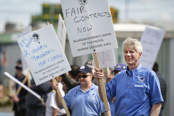Alaska Marine Highway System sewards Jeff Chapman, right, and Jay Beasley picket Inlandboatmen's Union of the Pacific after failing to reach agreement on a contract with the state of Alaska, Wednesday, July 24, 2019, in Ketchikan, Alaska. (Dustin Safranek/Ketchikan Daily News via AP)