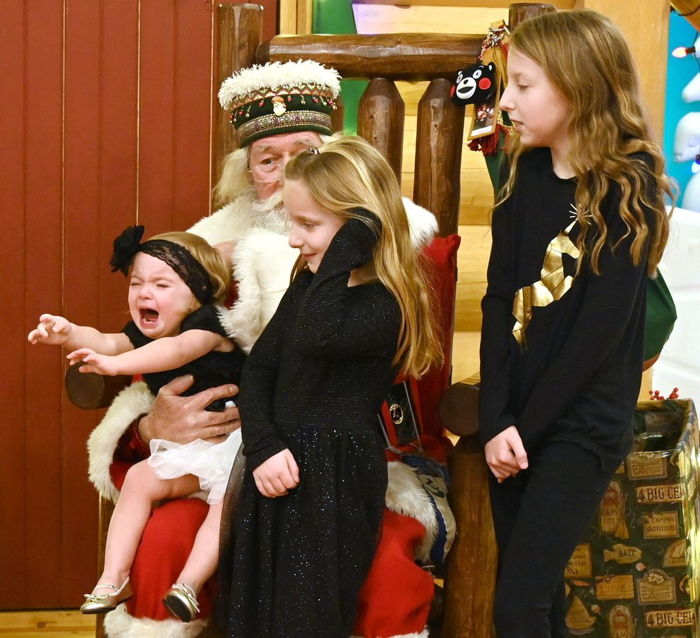 Santa Paul hangs onto an unhappy Anistyn Durst, 1, while her sisters Paityn, 6, and Aslynn, 10, wait. The portrait was finally taken when the whole family, parents Zack and Katie Durst joined the group. (Anne Raup / ADN)