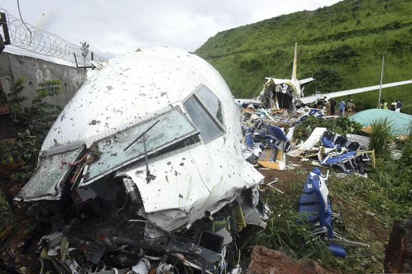 People stand by the debris of the Air India Express flight that skidded off a runway while landing in Kozhikode, Kerala state, India, Saturday, Aug. 8, 2020. The special evacuation flight bringing people home to India who had been trapped abroad because of the coronavirus skidded off the runway and split in two while landing in heavy rain killing more than a dozen people and injuring dozens more. (AP Photo/Shijith Sreedhar)